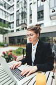 Portrait Of Female Freelancer Wearing Glasses With Computer. Young Business Woman Sitting At Coffee  poster