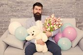 Best Boyfriend Ever. Romantic Man With Flowers And Teddy Bear Sit On Couch Waiting Girlfriend. Roman poster