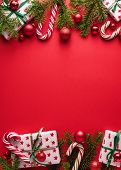 Red Merry Christmas and New Year background. Decorative border of fir branches, gifts, Christmas bal poster