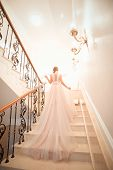 A Girl In A Wedding Dress Is Walking Up The Stairs. Beige Dress. Beautiful Lady In Luxurious Ballroo poster