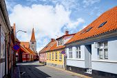 Streets Of A Small Danish Village With Red Rooftops In The Summer Sun Under A Blue Sky poster
