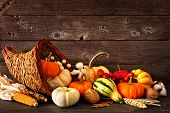 Thanksgiving Cornucopia Filled With Autumn Pumpkins And Vegetables Against A Rustic Dark Wood Backgr poster