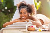 Young african woman getting spa massage outdoor in a tropical environment. Happy woman lying on mass poster