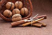 Walnuts in a wicker basket and cinnamon