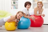 People exercising with large rubber balls - health education in children