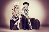 Cute little boy with his old saxophone is sitting on a suitcase with charming little lady. Retro sty
