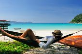 Woman in hammock on tropical beach at Perhentian islands, Malaysia