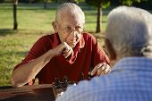 stock photo of time-piece  - Active retired people old friends and free time two senior men having fun and playing chess at park - JPG