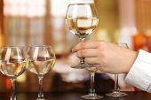 Tasting white wine on room background