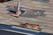 stock photo of blown-up  - A close up view of shingles being blown off a roof and other roof damage - JPG