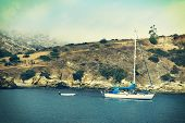 stock photo of dingy  - A sailboat and dingy anchored in a bay at Catalina Island - JPG