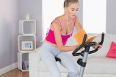 Sporty unsmiling blonde training on exercise bike reading a book in bright living room