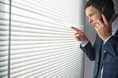 Unsmiling handsome businessman looking through roller blind phoning in dark room