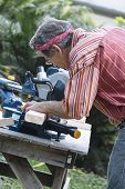 Man Sawing Wood With Sliding Compound Miter Saw
