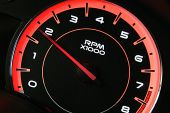 foto of speedo  - Vehicle tachometer with red back lighting displayed at an angle with black background - JPG