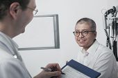 Doctor writing on medical chart with smiling patient