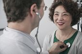 Doctor checking heartbeat of a patient with a stethoscope