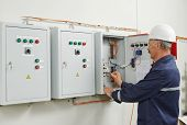 image of electrician  - senior adult electrician builder engineer testing equipment in fuse box - JPG