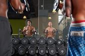 Mirror reflection of two men exercising in a gym