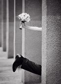 leg of the bride and groom with a bouquet of hand, black and white