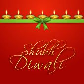 Beautiful greeting card on occasion of Indian festival of lights, decorated with illuminated tradition oil lit lamps, green ribbon on red background with golden text Shubh Diwali (Happy Diwali).