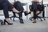 Three business people with legs crossed sitting on chairs