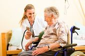 stock photo of pressure  - Young nurse and female senior in nursing home - JPG