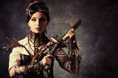 stock photo of guns  - Portrait of a beautiful steampunk woman holding a gun over grunge background - JPG