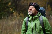 Happy mature backpacker in an autumn forest