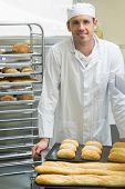 stock photo of baguette  - Young male baker standing in a kitchen in front of baguettes and rolls - JPG