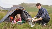 Smiling couple cooking outside on camping trip in the countryside