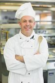 Mature head chef smiling at camera holding a wooden spoon