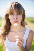 Pretty young woman blowing on dandelion at camera making a wish