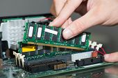 foto of cpu  - Close up of fingers holding piece of hardware lying on desk - JPG