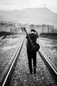image of red back  - Young male musician walking with his acustic guitar - JPG