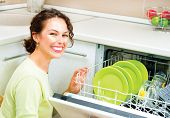 Dishwasher. Happy Young woman in the Kitchen doing Housework. Dishwasher Machine, dishwashing. Wash-