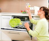 Dishwasher. Happy Young woman in the Kitchen doing Housework. Dishwasher Machine, dishwashing. Wash-up. Smiling Girl using dishwasher machine