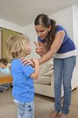 stock photo of misbehaving  - Woman scolds a young child in the home. Another child can be seen in the background