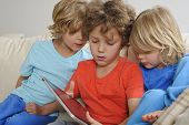 3 boys playing games on a tablet