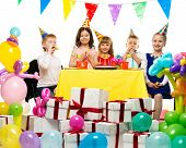 Croup of happy children celebrating birthday behind table