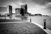 stock photo of pov  - Long exposure of skyscrapers in Harbor East seen from the Waterfront Promenade at the Inner Harbor in Baltimore Maryland - JPG