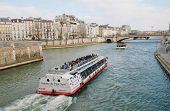 PARIS, FRANCE - MARCH 18, 2014: Excursion boats head towards the Pont De La Tournelle on the River S