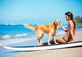 Attractive Young Woman Enjoying Sunny Day at the Beach with her Dog, Golden Retriever