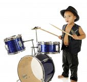 An adorable, barefoot preschooler dressed as a rock star, beating on a drum set.  On a white backgro