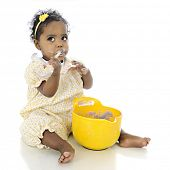 image of snitch  - An adorable baby girl looking up questioningly while eating pudding from a mixing bowl before her - JPG