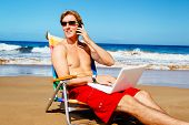 Young Attractive Casual Businessman Entrepreneur Relaxing at the Beach with Laptop Computer Talking