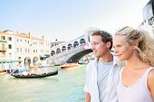 Venice couple by Rialto Bridge on Grand Canal on travel together. Young happy couple on holidays or