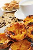 closeup of some pasteis de nata and some pasteis de feijao, typical Portuguese pastries, on a set table
