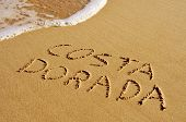 Costa Dorada, the name of an area of the Mediterranean coast of Spain, written in the sand of a beac