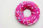 a donut coated with a pink frosting and sprinkles of different colors soaking in milk